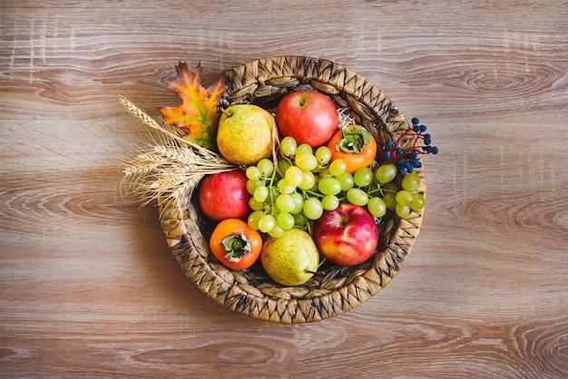 Vista dall'alto di vari frutti autunnali colorati in un cesto di vimini sul tavolo di legno.