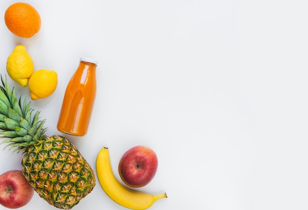 Vista dall'alto di vari frutti e una bottiglia di succo multivitaminico appena spremuto su uno sfondo bianco. copia spazio. disteso.