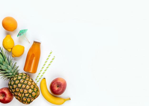 Vista dall'alto di vari frutti, una bottiglia di succo multivitaminico appena spremuto e accessori cocktail su uno sfondo bianco. copia spazio. disteso.