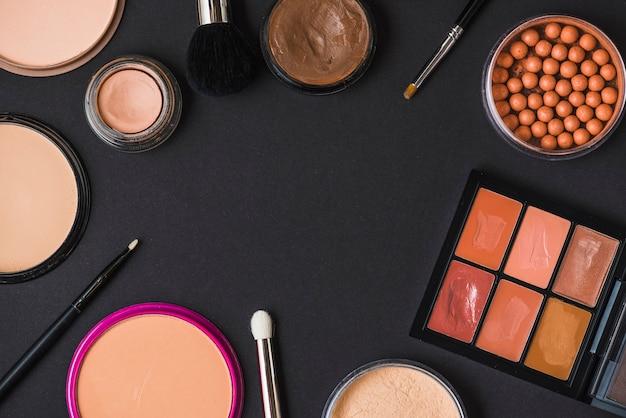 Vista dall'alto di vari prodotti cosmetici che formano cornice sulla superficie nera