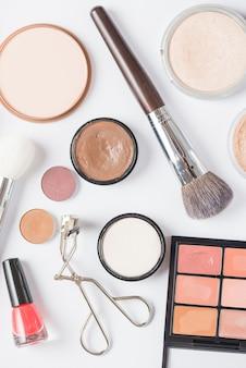 Vista dall'alto di vari prodotti cosmetici su sfondo bianco