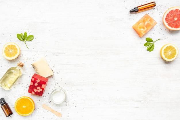 Vista dall'alto di vari saponi organici fatti a mano colorati disposti con agrumi, erbe, semi di chia e aloe.