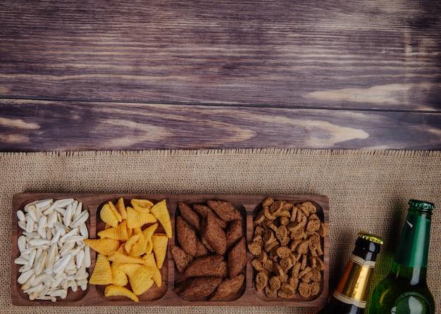 Vista dall'alto di vari spuntini di birra patatine e semi di girasole su un piatto di legno con bottiglie di birra vestirono su rustico su rustico con spazio di copia