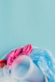 Vista dall'alto di vari tipi di rifiuti di plastica usa e getta su sfondo blu, copia spazio