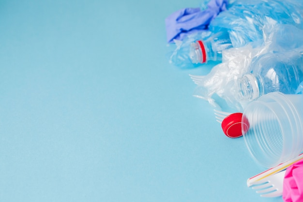 Vista dall'alto di vari tipi di rifiuti di plastica usa e getta su sfondo blu