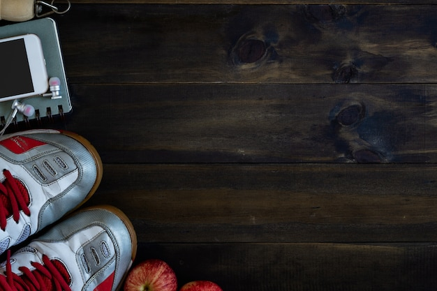 Vista dall'alto di vecchie scarpe sportive, smart phone con cuffie, corda per saltare e mele