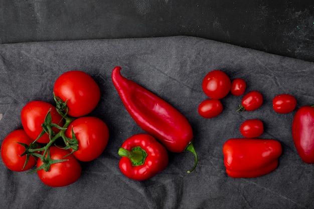 Vista dall'alto di verdure come pomodoro intero e pepe sulla superficie del panno e superficie nera
