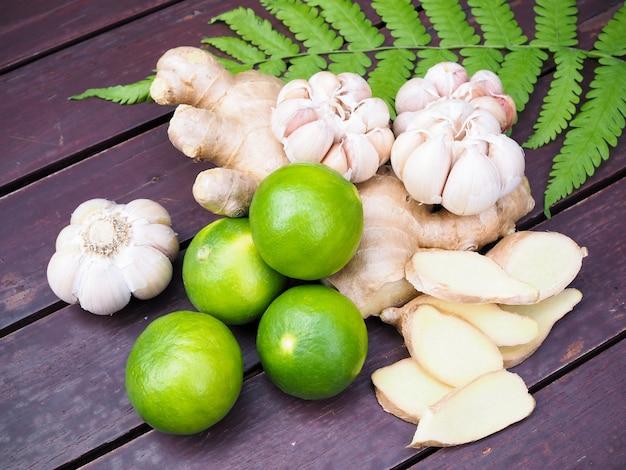 Vista dall'alto di verdure ed erbe per cucinare con radice di curcuma, zenzero, aglio e frutta al limone.