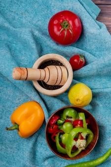 Vista dall'alto di verdure intere e fette di peperoni e pomodori con limone e pepe nero nel frantoio di aglio sul panno blu