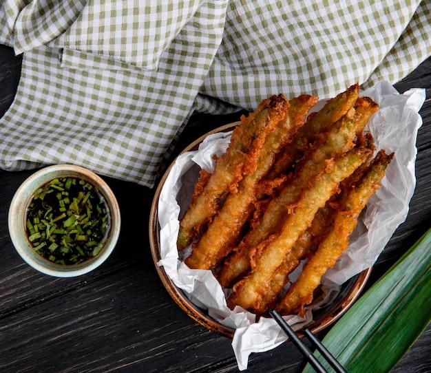 Vista dall'alto di verdure tempura in una ciotola servita con salsa di soia su legno con tessuto a quadri