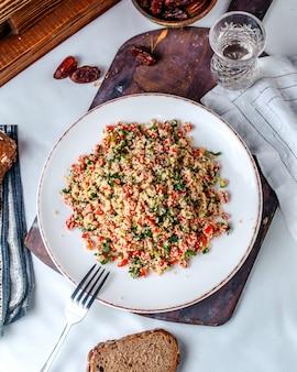 Vista dall'alto di verdure tritate colorate vitamina arricchite all'interno del piatto bianco sul pavimento chiaro