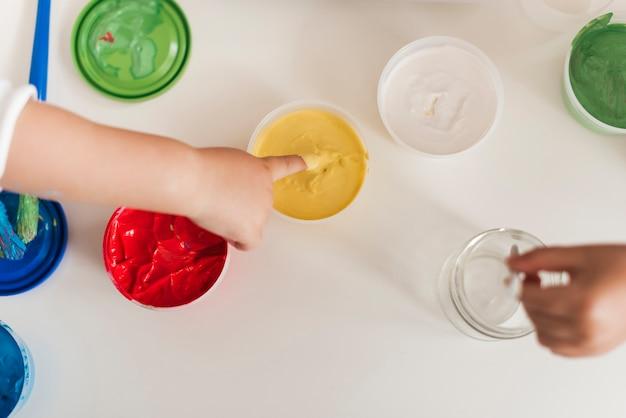 Vista dall'alto di vernice e mani del bambino