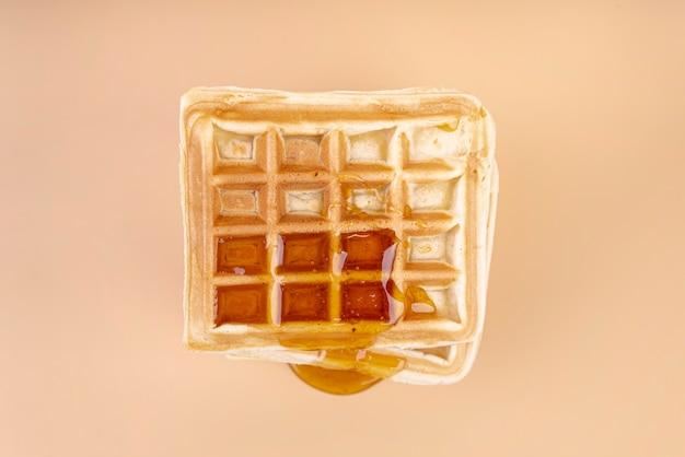 Vista dall'alto di waffle con miele gocciolante