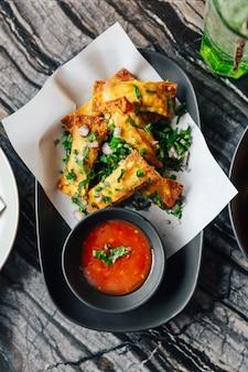 Vista dall'alto di wontons di formaggio fritto cospargere con scalogno e scalogno servito con salsa al peperoncino.