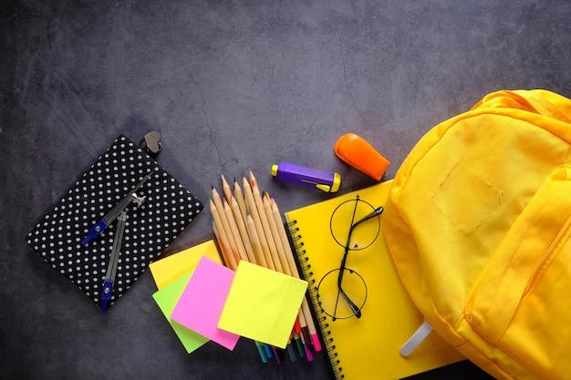 Vista dall'alto di zaino giallo con diversi elementi decorativi colorati sul tavolo.
