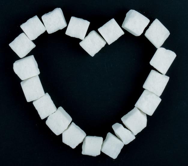 Vista dall'alto di zollette di zucchero disposte a forma di cuore su sfondo nero
