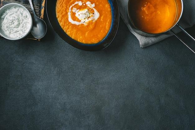 Vista dall'alto di zuppa di zucca in un piatto e una pentola