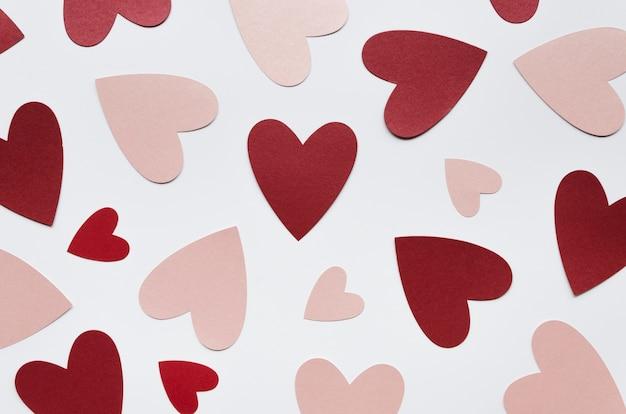 Vista dall'alto diverse forme di cuore rosso e rosa sul tavolo