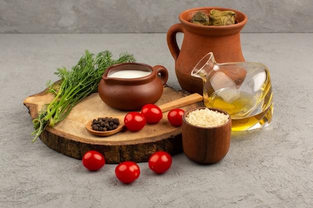 Vista dall'alto dolma in pentola con pomodorini rossi olio d'oliva e yogurt sul pavimento grigio