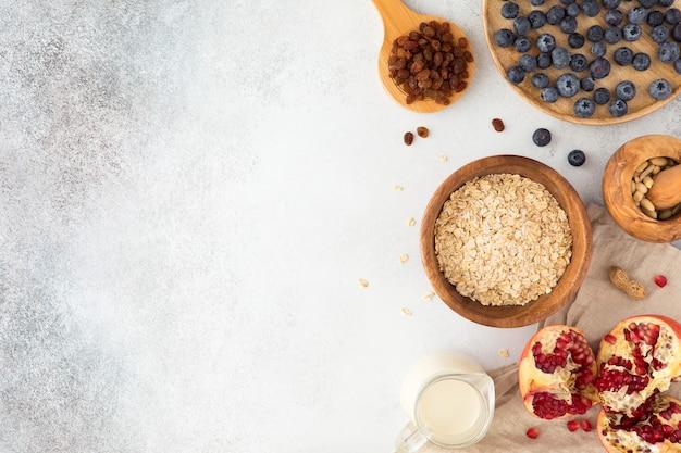 Vista dall'alto e laici piatta di porridge di farina d'avena in articoli in legno con latte, ribes, mirtilli, mandorle e granato sul tavolo luminoso in cemento strutturato.