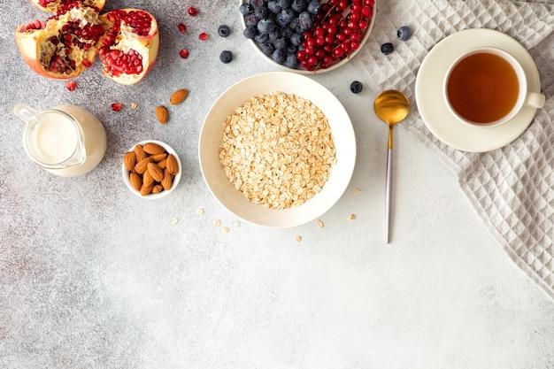 Vista dall'alto e piatto disteso di porridge di farina d'avena con latte, ribes, mirtilli, mandorle e granato sul tavolo luminoso in cemento strutturato.