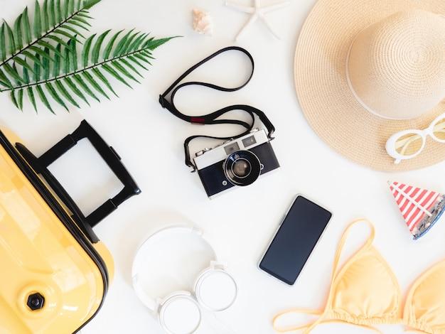 Vista dall'alto elementi di viaggio con bikini, valigie e attrezzatura da viaggio. elementi essenziali per il turismo, effetto tono vintage