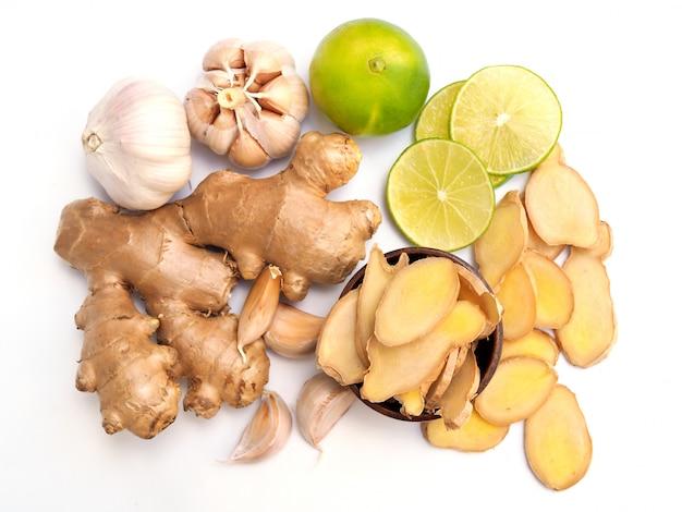 Vista dall'alto erbe e spezie con radice di zenzero e agrumi limone lime e aglio isolato su sfondo bianco