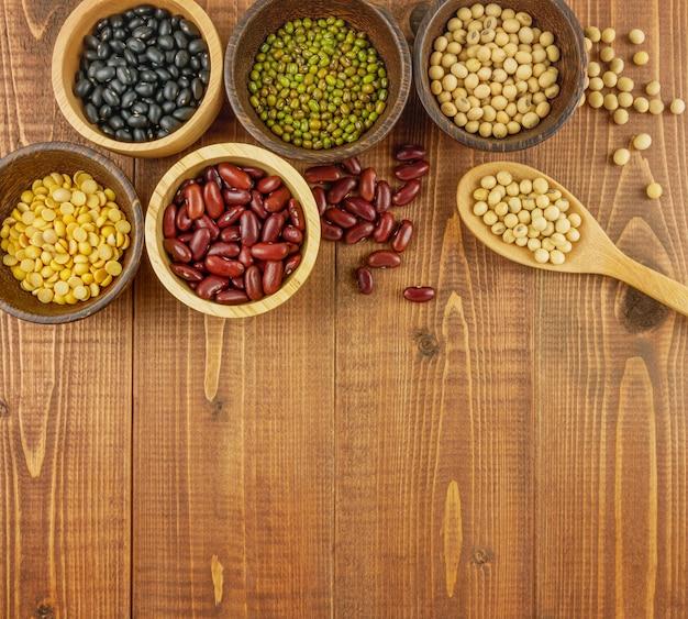 Vista dall'alto, fagioli assortiti vista dall'alto compresi fagioli rossi, soia, fagioli neri, fagioli verdi su fondo di legno marrone, beige