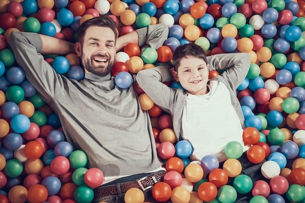 Vista dall'alto felice papà e figlio in piscina con le palle