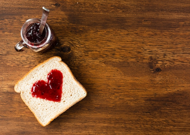 Vista dall'alto fetta di pane con cuore di marmellata