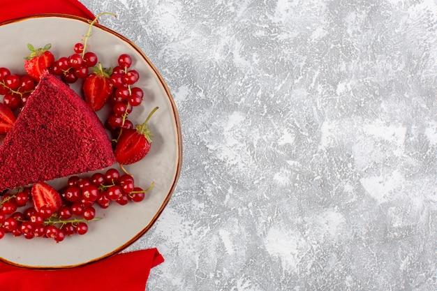 Vista dall'alto fetta di torta rossa fetta di torta di frutta all'interno del piatto con mirtilli rossi freschi e fragole sullo sfondo grigio torta di zucchero dolce biscotto