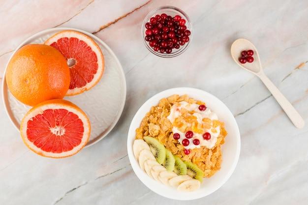 Vista dall'alto fette di pompelmo con yogurt e cornflakes