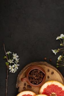 Vista dall'alto fette di pompelmo insieme a semi di caffè marrone su sfondo scuro
