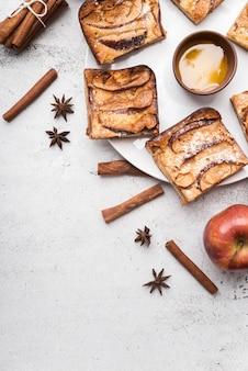 Vista dall'alto fette di torta e mela con bastoncini di cannella