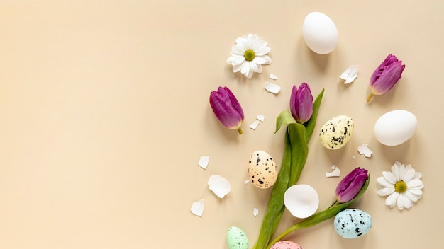 Vista dall'alto fiori e uova dipinte allineati sul tavolo