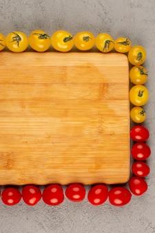 Vista dall'alto foderato di pomodori giallo rosso su sfondo grigio