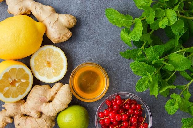 Vista dall'alto foglie di menta con limoni, zenzero, miele, ribes rosso