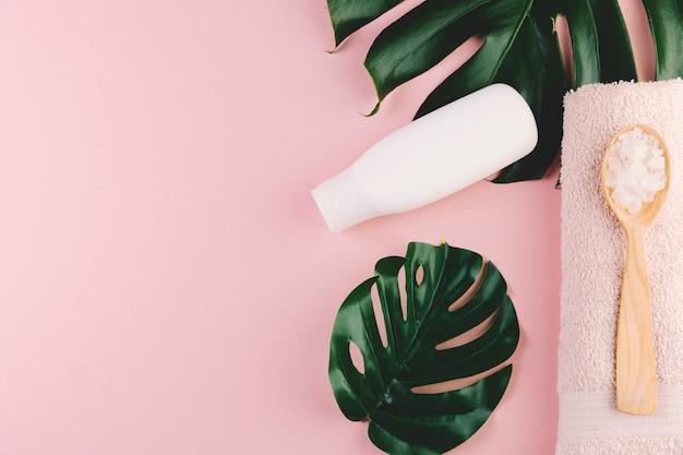 Vista dall'alto foglie tropicali con strumenti di bellezza e cosmetici