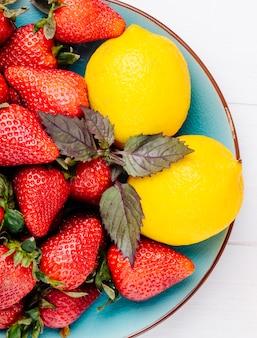 Vista dall'alto fragola con limone e basilico su un piatto