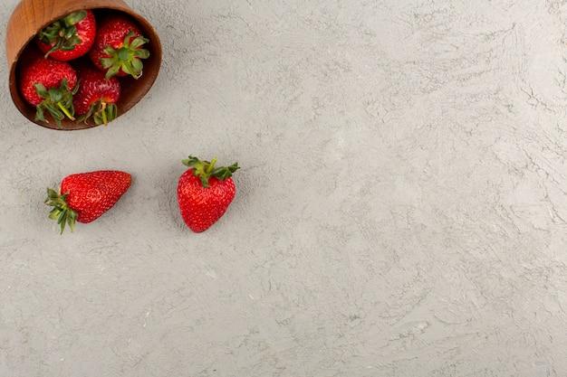 Vista dall'alto fragole rosse fresche morbide succose sullo sfondo grigio