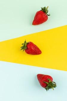 Vista dall'alto fragole rosso morbido isolato sul pavimento colorato