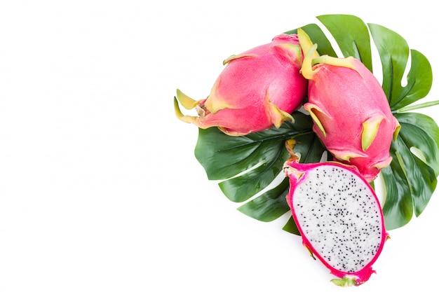Vista dall'alto frutto del drago, fetta di pitaya e foglie verdi isolati su bianco con tracciato di ritaglio