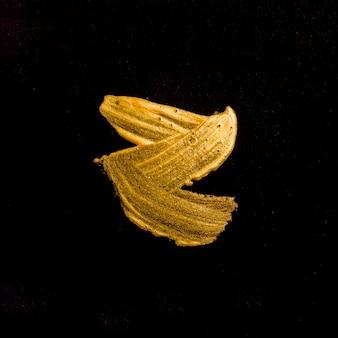 Vista dall'alto fuso di vernice dorata su sfondo nero