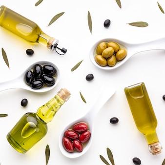 Vista dall'alto giallo olive nere rosse in cucchiai con foglie e bottiglie di olio