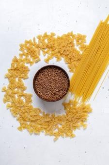 Vista dall'alto giallo pasta cruda poco formata e lunga con piatto di grano saraceno sulla scrivania bianca pasta italia cibo pasto