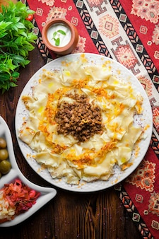 Vista dall'alto guru azero khingal pasta caucasica con carne tritata fritta e cipolla con salsa di panna acida e sottaceti su una tovaglia verticale