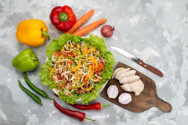 Vista dall'alto gustosa insalata di verdure con verdure a fette e intere verdure fresche e petto di pollo crudo su grigio, pasto di cibo insalata