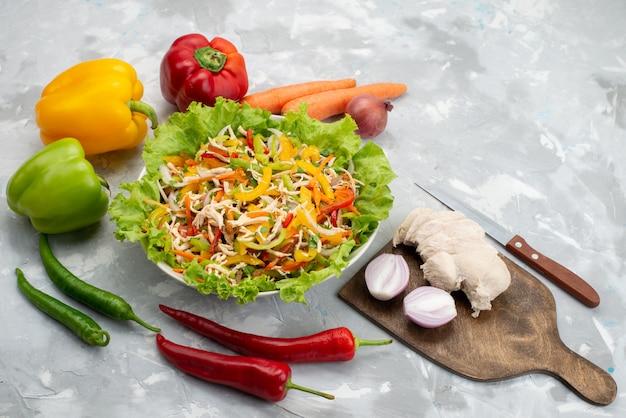 Vista dall'alto gustosa insalata di verdure con verdure a fette e intere verdure fresche e petto di pollo crudo su grigio, pasto di insalata
