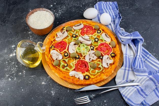 Vista dall'alto gustosa pizza ai funghi con pomodori rossi, olive, peperoni e funghi, tutti affettati all'interno con uova sulla pizza scura del cibo della scrivania