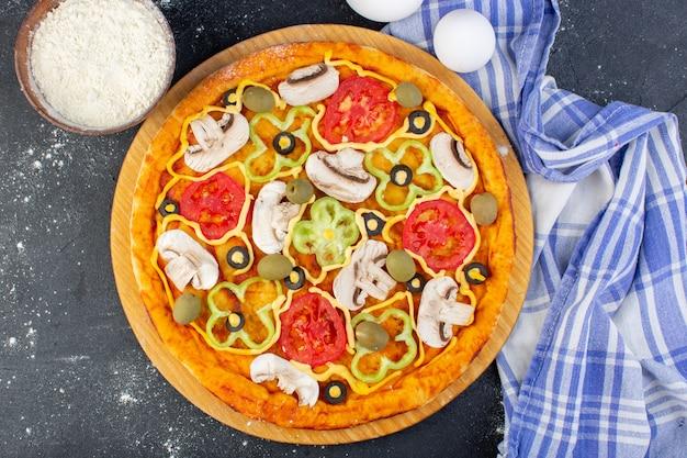 Vista dall'alto gustosa pizza ai funghi con pomodori rossi peperoni olive e funghi tutti affettati all'interno con uova sull'impasto della pizza pasto scuro della scrivania